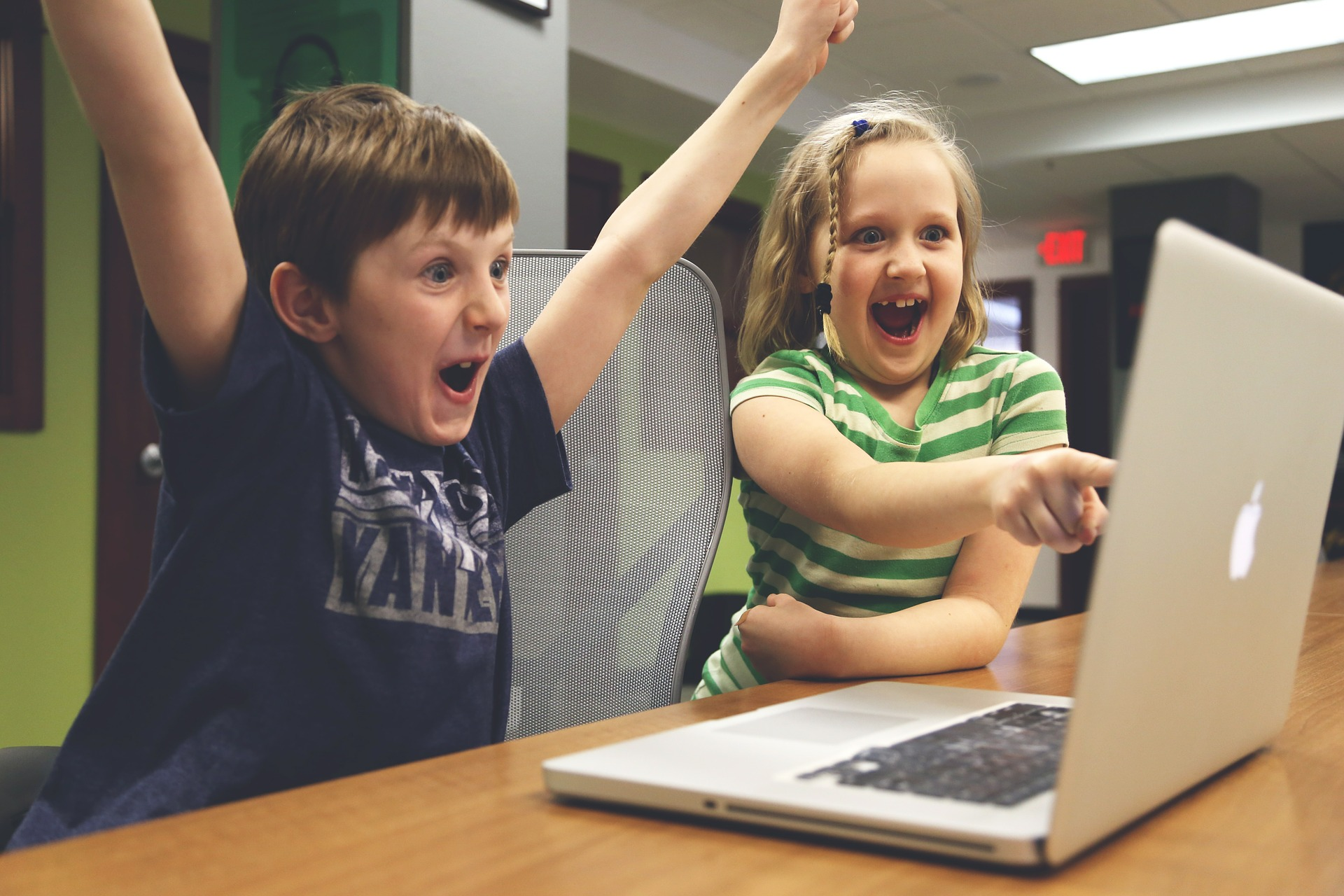 Happy children pointing at laptop